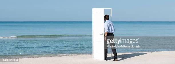 Man walking into open door on beach, rear view