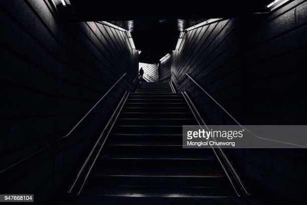 man walking into the light in the dark tunnel from underground - black and white stock-fotos und bilder