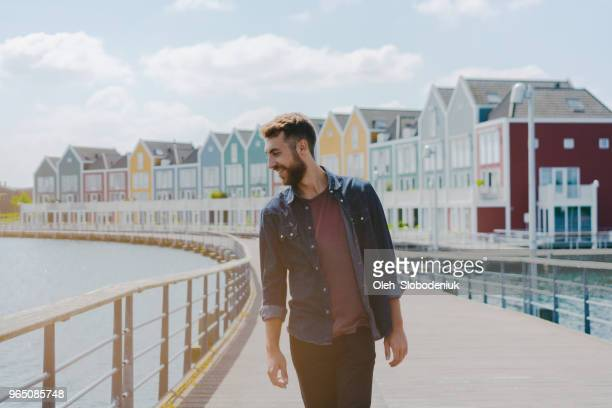man walking near colorful buildings near the lake - rotterdam stock pictures, royalty-free photos & images