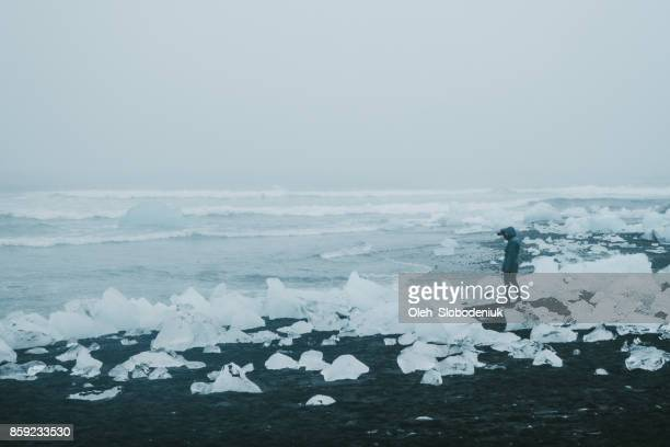 man  walking near jokulsarlon lagoon - glacier lagoon stock photos and pictures
