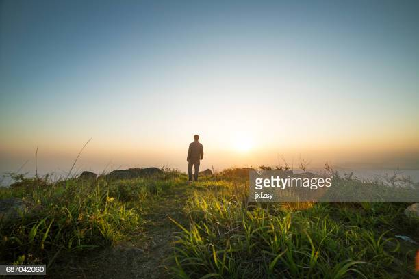 man walking near sunset on top of mountain - hill stock pictures, royalty-free photos & images