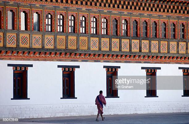 Man walking next to the Tashichho Dzong, home of the Government, Royal Palace and Religious Centre, in Thimpu, Bhutan.