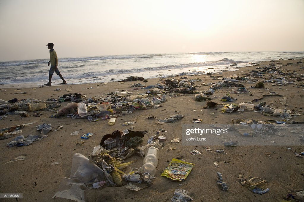 Man walking on a beach full of garbage : Stock Photo