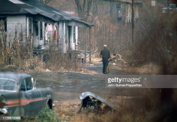 A man walking on a dirt road followed by a dog Pike County Kentucky US 1967