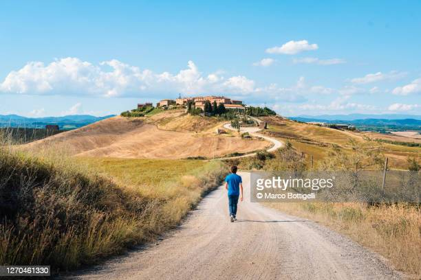 man walking on a gravel road to a rural village, tuscany - exploration stock pictures, royalty-free photos & images