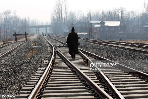Man walking on a railway track as train service suspend on Saturday for security reasons in the Kashmir valley in view of a shutdown call given by...