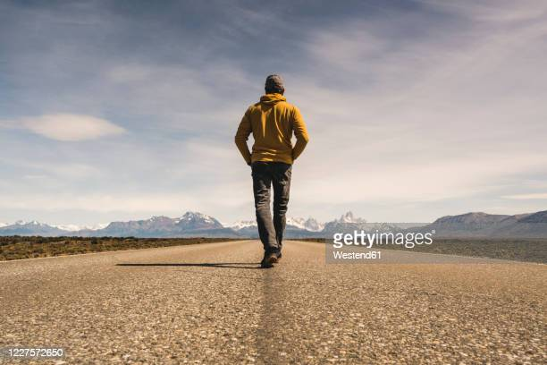 man walking on a road in remote landscape in patagonia, argentina - jacket stock pictures, royalty-free photos & images