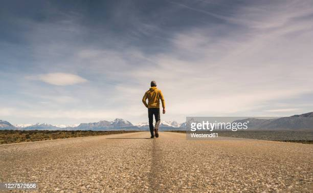 man walking on a road in remote landscape in patagonia, argentina - yellow coat stock pictures, royalty-free photos & images