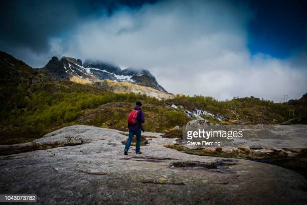 Man walking on a wilderness trail in the Lofoten Islands, Norway.