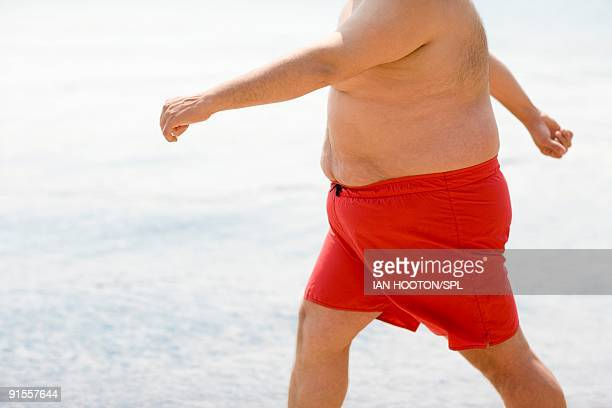 man walking on beach - fat man on beach stock photos and pictures
