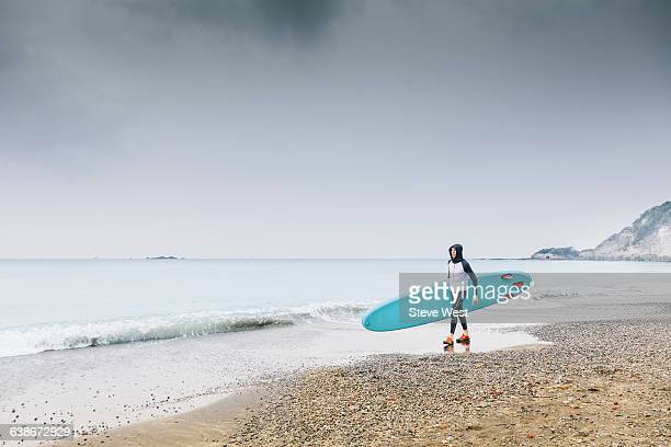 Man walking on beach with Paddleboard (SUP)