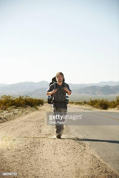 Man walking on desert road.