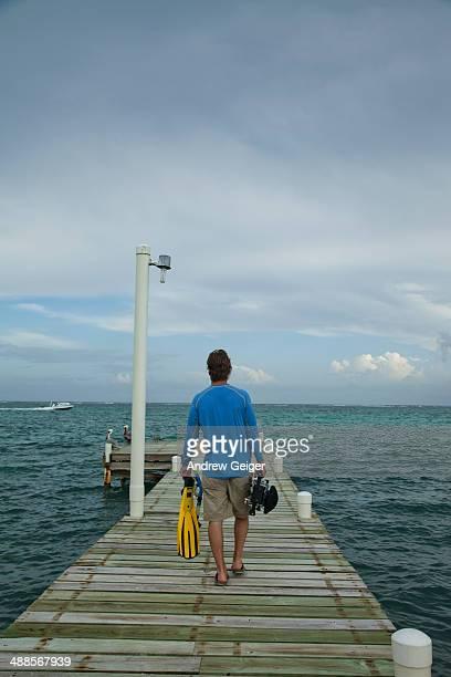 man walking on dock with swim fins and camera. - pantaloncini grigi foto e immagini stock