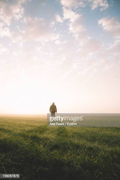 Man Walking On Field Against Sky During Sunset