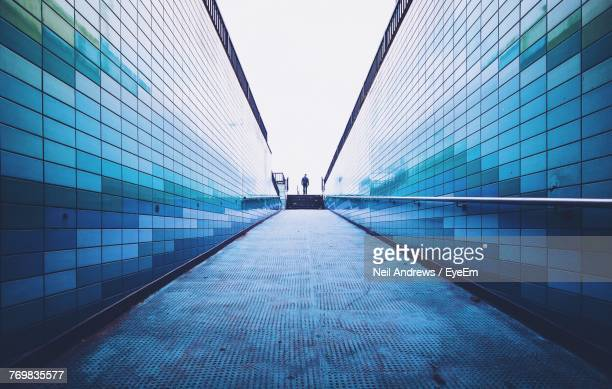man walking on footpath amidst surrounding wall - heldere lucht stockfoto's en -beelden