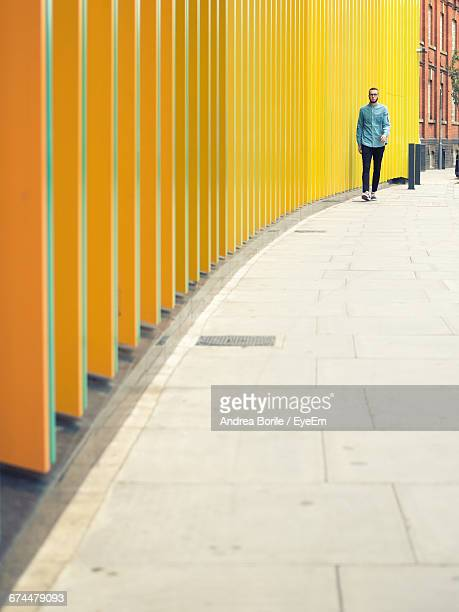 Man Walking On Footpath By Modern Yellow Building In City