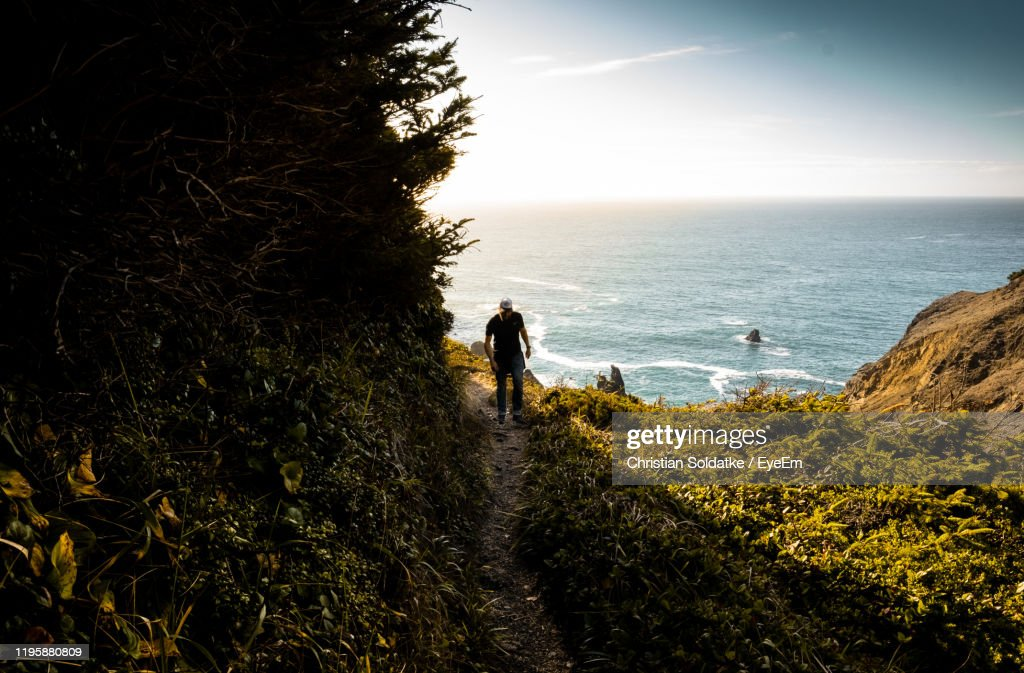 Man Walking On Land Against Sea And Sky : Stock-Foto