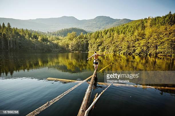 Man walking on log in alpine lake