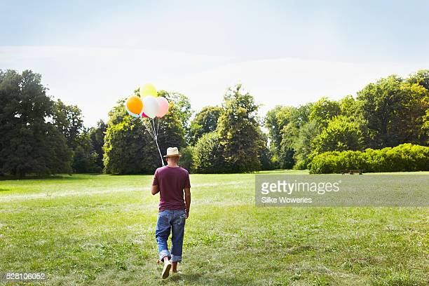 Man walking on meadow holding bunch of colorful balloons
