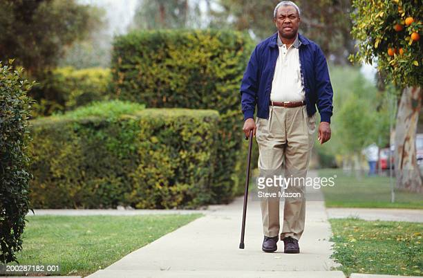 man walking on path in park - walking cane stock pictures, royalty-free photos & images
