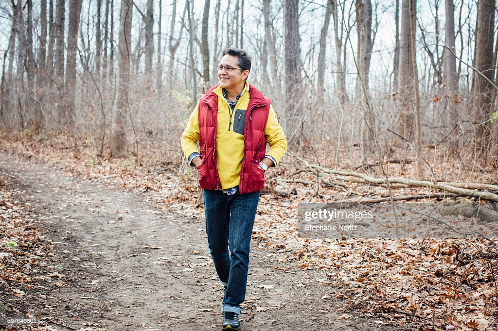 Man Walking On Path Through Forest Smiling : Stock Photo