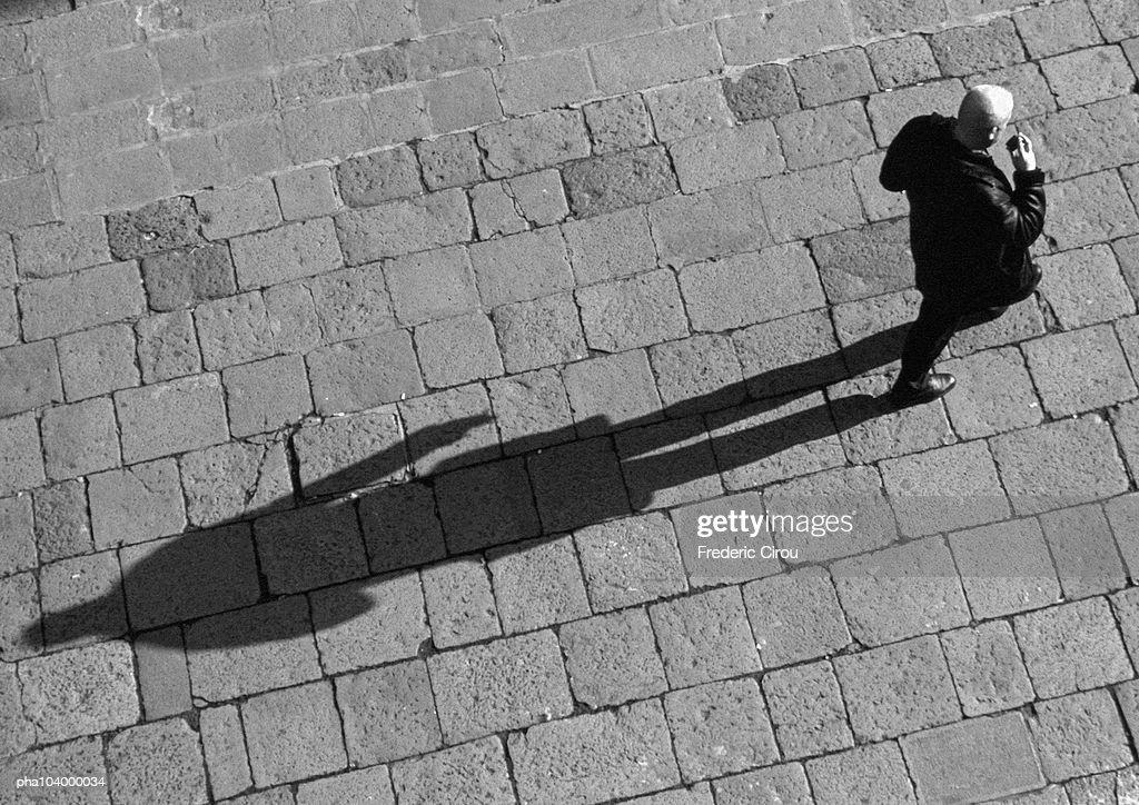 Man walking on pavement, elevated view, b&w : Stockfoto