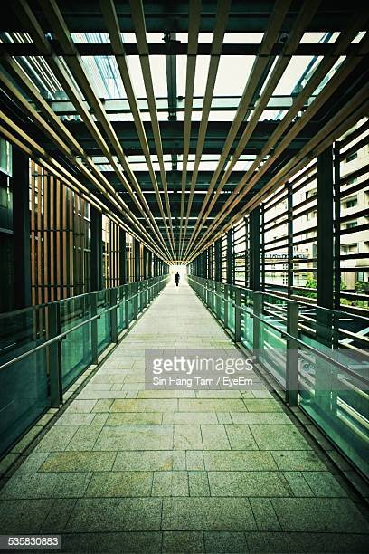 Man Walking On Pedestrian Walkway Bridge In City