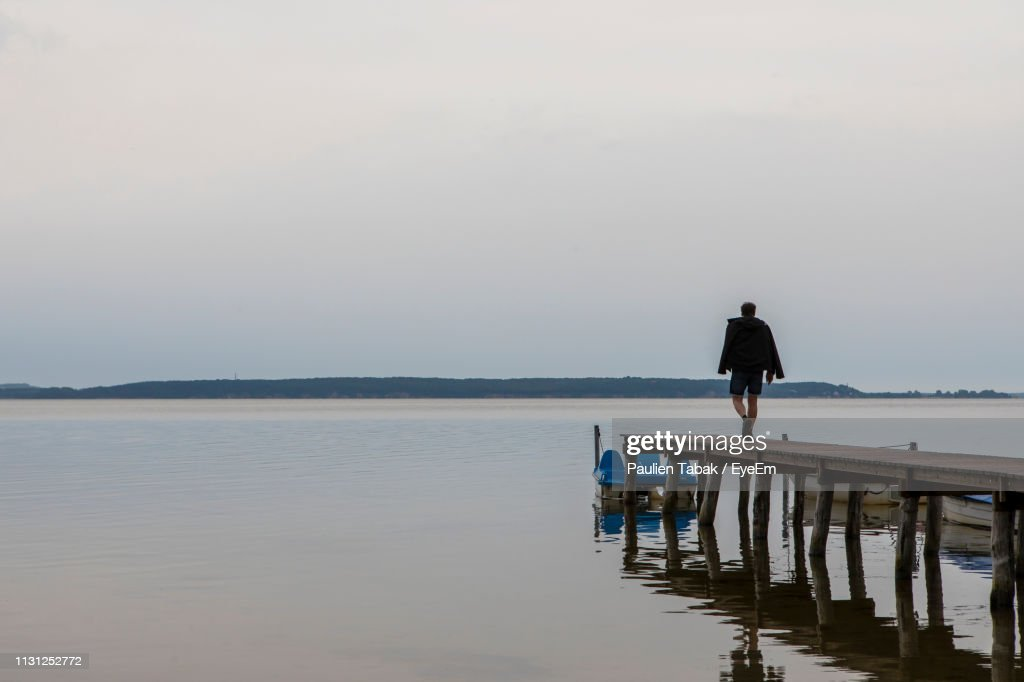 Man Walking On Pier Over Sea Against Sky : Stockfoto