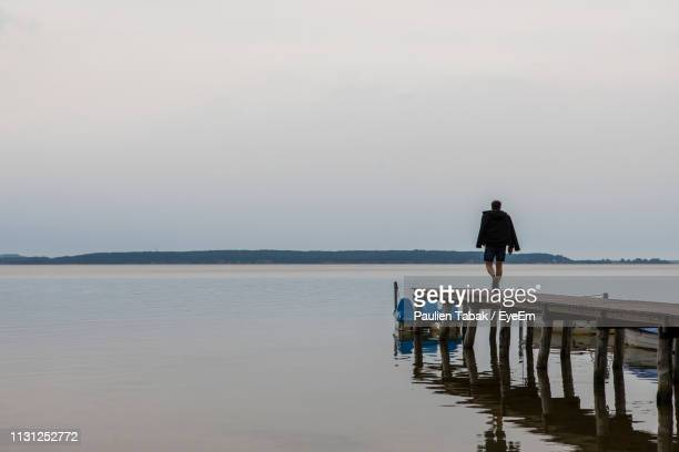 Man Walking On Pier Over Sea Against Sky