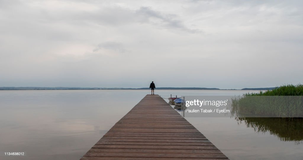 Man Walking On Pier Over Sea Against Sky : Stock Photo