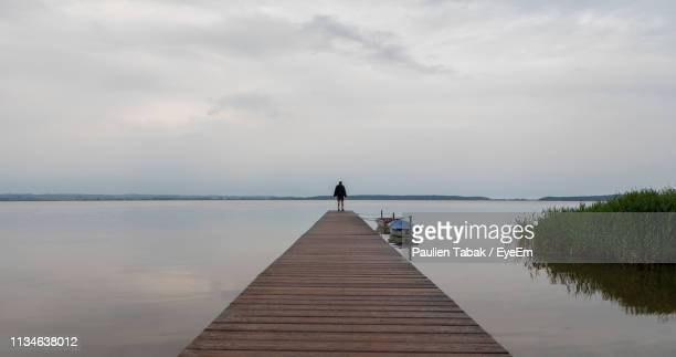 man walking on pier over sea against sky - paulien tabak stock pictures, royalty-free photos & images