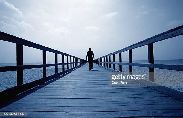 man walking on pier, rear view (digital enhancement) - descrição geral - fotografias e filmes do acervo