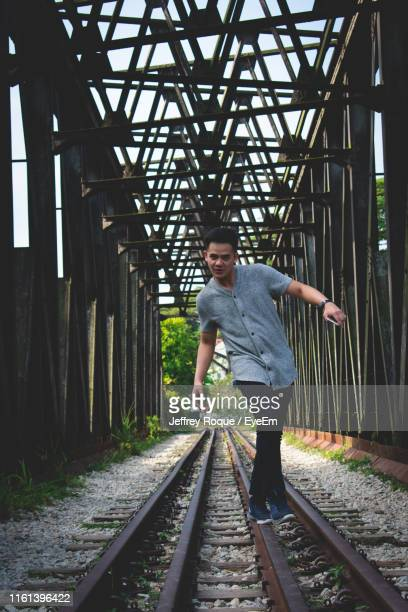 man walking on railroad track - jeffrey roque stock photos and pictures