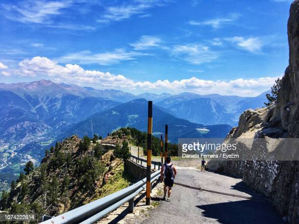 man walking on road amidst mountains against blue sky - andorra la vella stock pictures, royalty-free photos & images