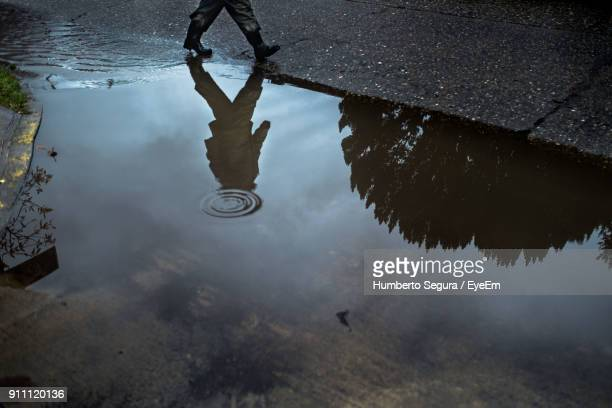 man walking on road with reflection in puddle - partie inférieure photos et images de collection