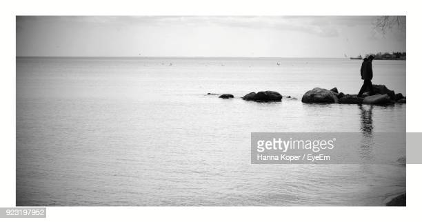 man walking on rocks over sea at beach - koper stock photos and pictures
