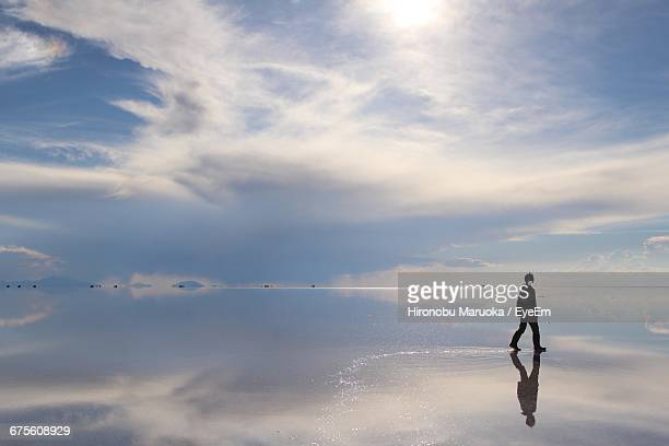 Man Walking On Salt Flat Against Sky At Salar De Uyuni