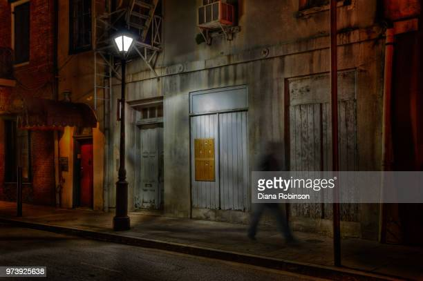 man walking on sidewalk at night, french quarter, new orleans, usa - new orleans city stock pictures, royalty-free photos & images