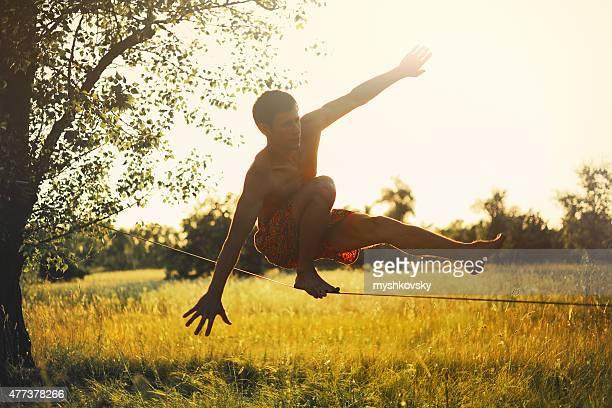 Man walking on slackline in the meadow 夕暮れます。
