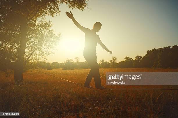 Mann zu Fuß auf der slackline in der Wiese bei Sonnenuntergang.