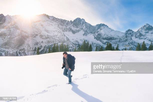 Man Walking On Snow Covered Field By Mountain