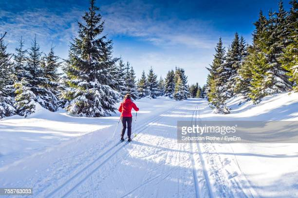 man walking on snow covered trees against sky - hill stock pictures, royalty-free photos & images
