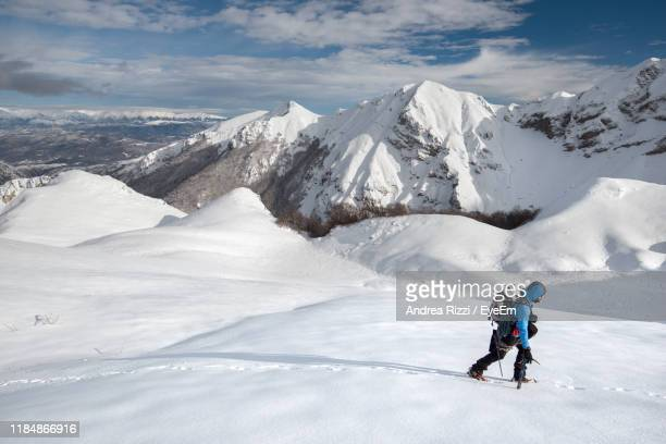 man walking on snowcapped mountains during winter - andrea rizzi photos et images de collection