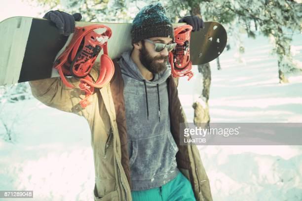 男の肩にスノーボードと雪道を歩いて