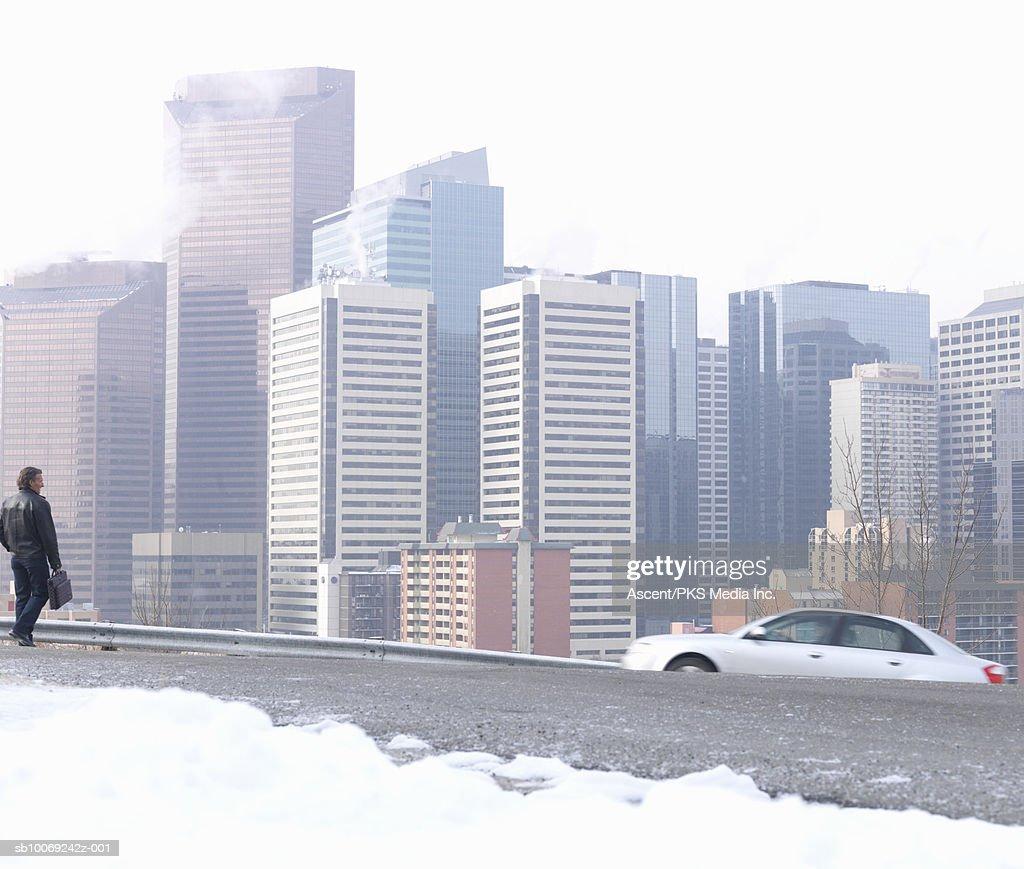 Man walking on snowy street, city skyline in background : Stockfoto