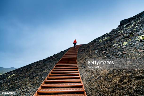 man walking on stairs on a mountain against blue sky - gradino foto e immagini stock