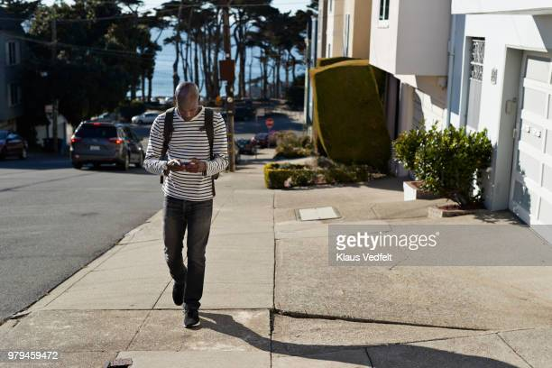Man walking on steep road and checking smartphone