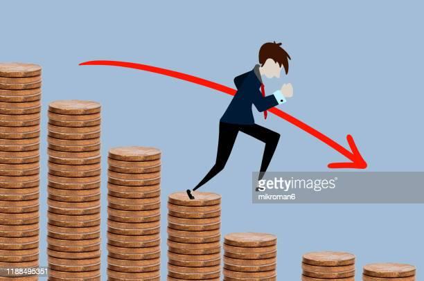 man walking on steps made of coins - zinssatz stock-fotos und bilder