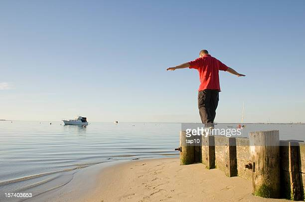 Man walking on stones near the sea