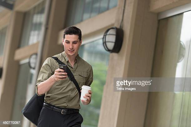 Man walking on street and text messaging